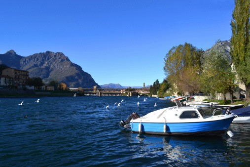 All-inclusive vacations- Motorboats anchored at Lecco and white seagulls flying.