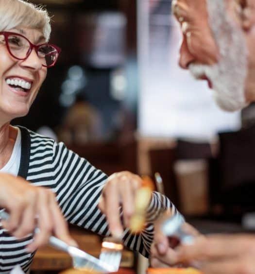 active senior couple eating dinner